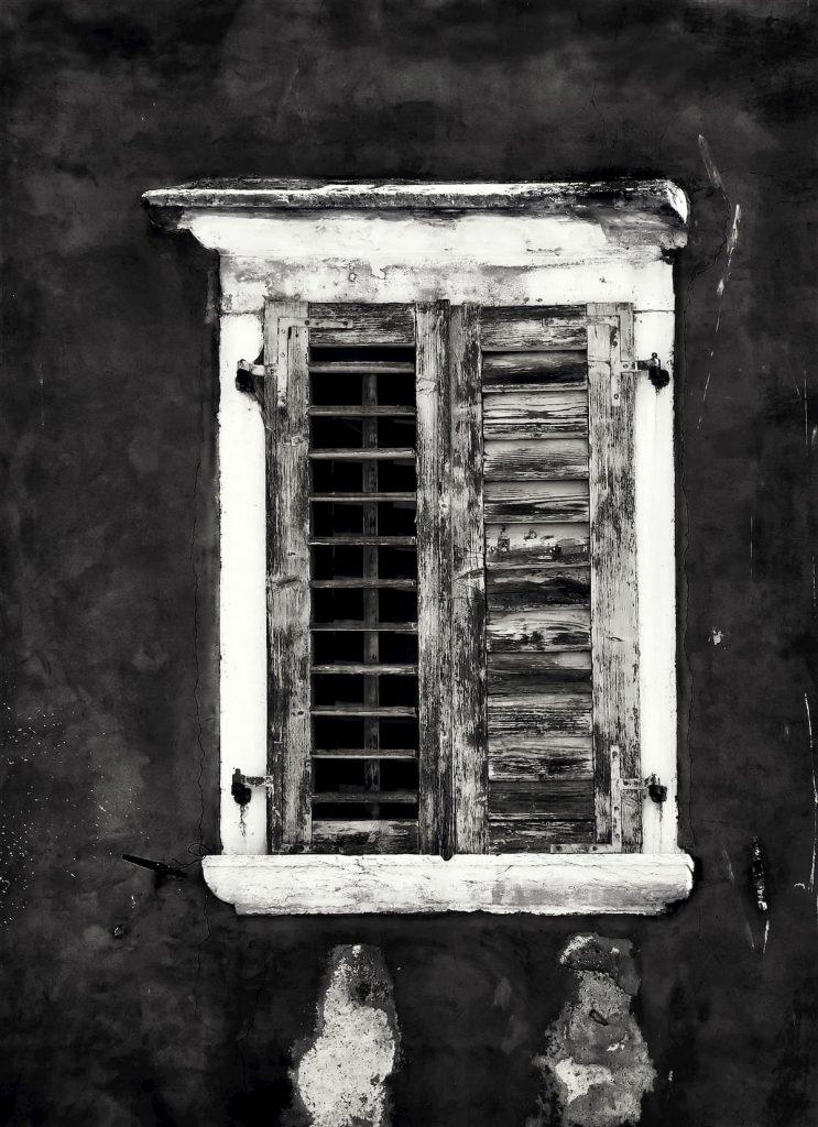 Staré okno s drevenými žalúziami