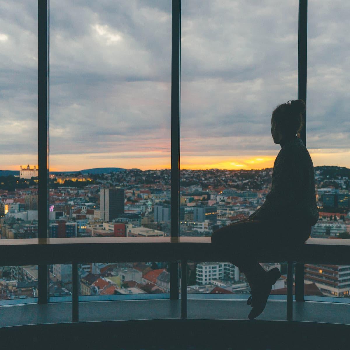 Žena sa pozerá z okna na mesto
