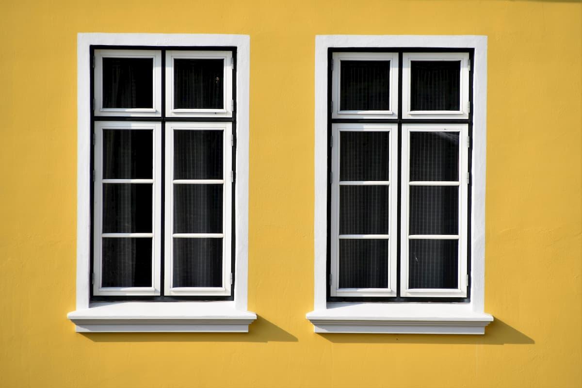 Biele drevené okná na žltom dome