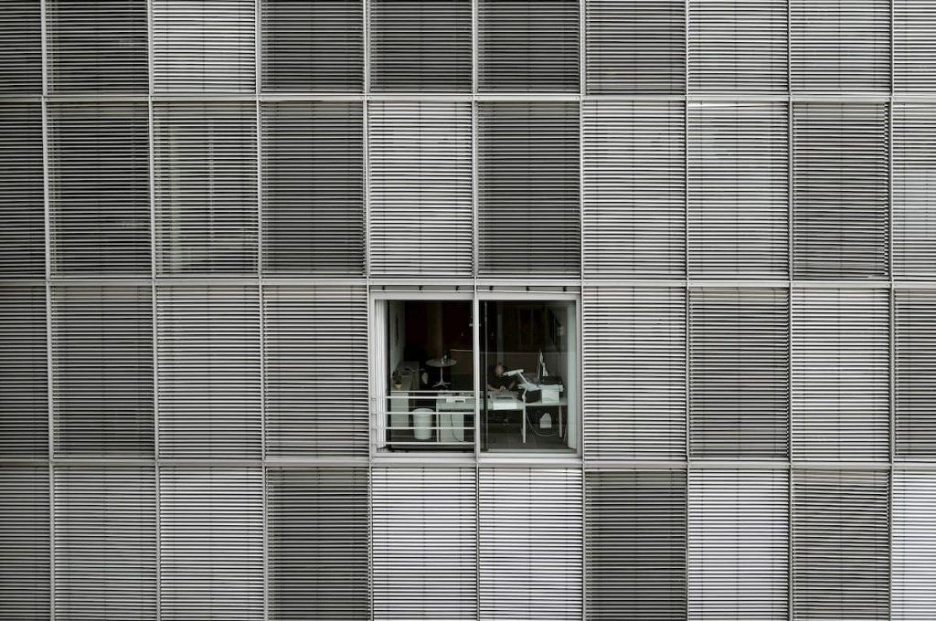 muž za oknom pracujúci v kancelárii